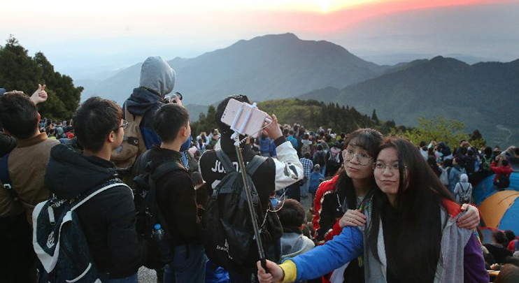 Tourists view sunrise at Hengshan Mountain scenic area in central China